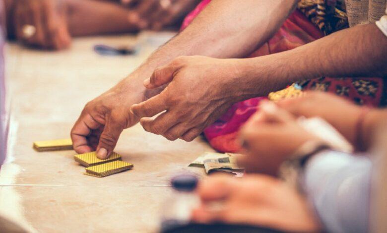 Muž drží v rukách hracie karty.