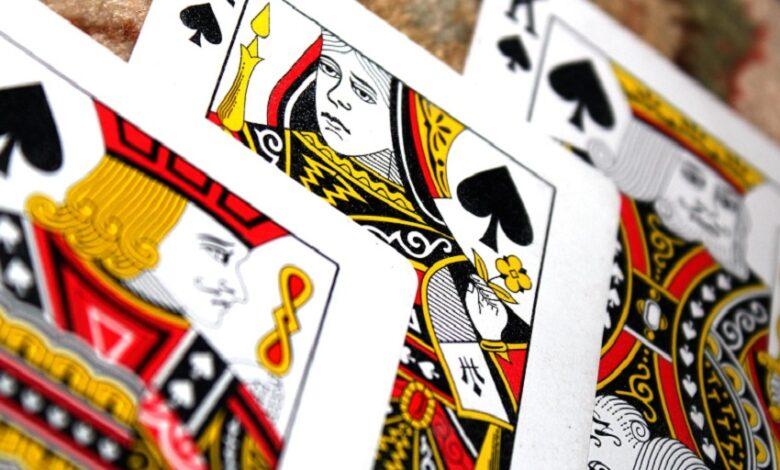 Tri hracie karty sú položené na koberci lícom nahor.